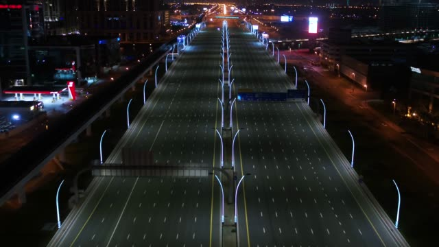 vídeos de stock e filmes b-roll de aerial view of empty streets at night in dubai, united arab emirates - covid flight