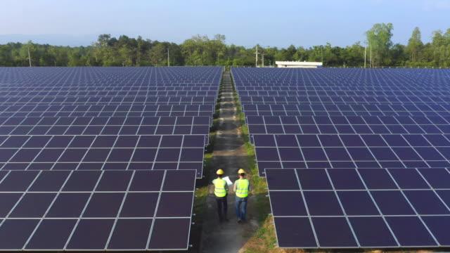 flygbild av ingenjör eller arbetstagare, människor, med solpaneler eller solceller på taket i gården. kraftverket med grönt fält, förnybar energikälla i thailand. eco-teknik för elkraft. - roof farm bildbanksvideor och videomaterial från bakom kulisserna