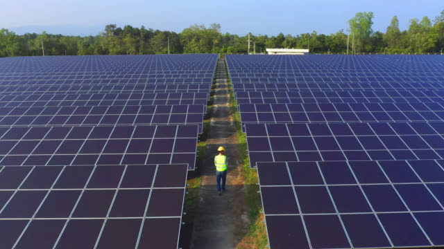 Aerial view of engineer or worker, people, with solar panels or solar cells on the roof in farm. Power plant with green field, renewable energy source in Thailand. Eco technology for electric power.