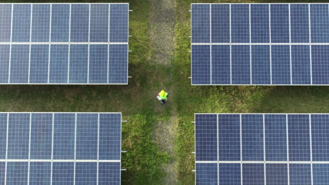 vídeos de stock e filmes b-roll de aerial view of engineering checking solar cell farm, electricity production from the sun, - energia solar