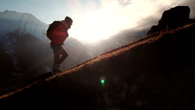 Aerial view of epic shot of a girl walking on the edge of the mountain as a silhouette in a beautiful sunset. Silhouette of a girl in a hat with a backpack climbing uphill