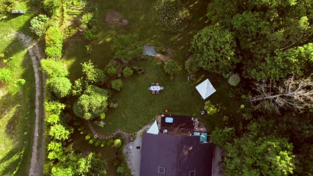 Vista aérea de la familia en la mesa de jardín para el almuerzo. - vídeo