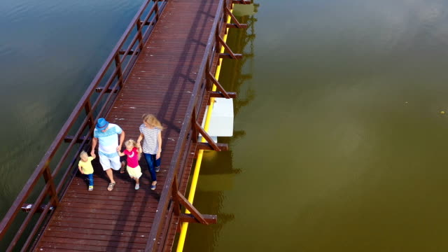 Aerial view of family walking together on bridge. Dad mom with son and daughter