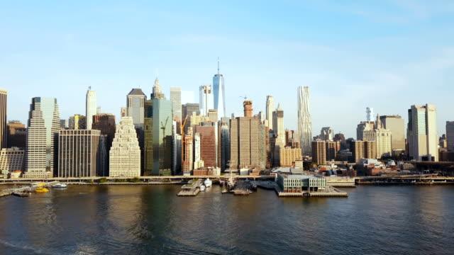 luftaufnahme des berühmten city, new york, amerika. drohne fliegen über den east river mit boot fahren durch und manhattan - manhattan stock-videos und b-roll-filmmaterial