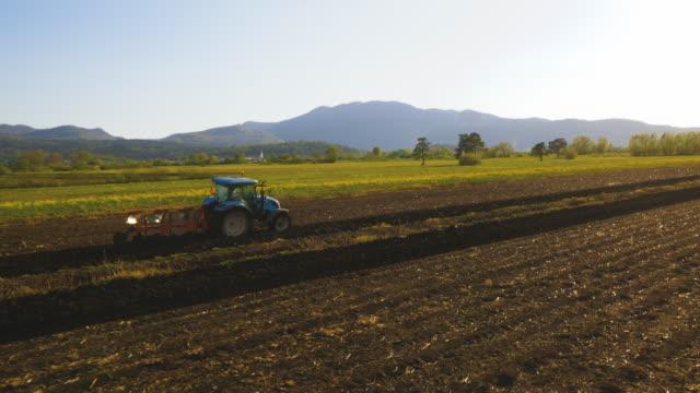 vidéos et rushes de vue aérienne de fermier cultivant le sol dans la campagne verte - foin