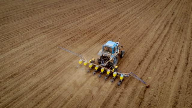 Flygbild av jordbrukare i traktor kombinera med seeder att så frön i marken och rullar hjulet i fält video