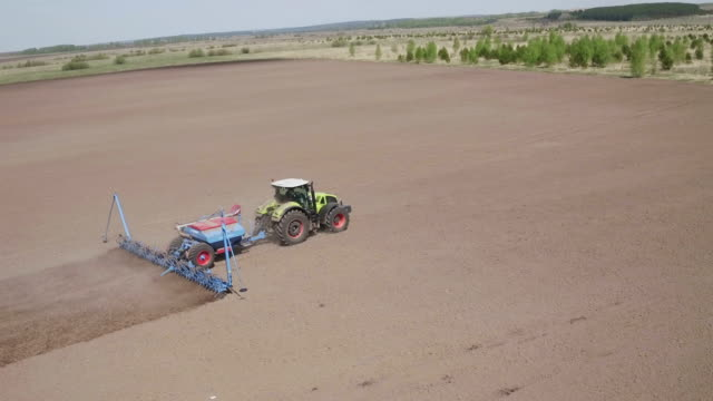 Aerial view of Farming tractor moving on agricultural field for sowing land. Agricultural tractor sowing farming field - video