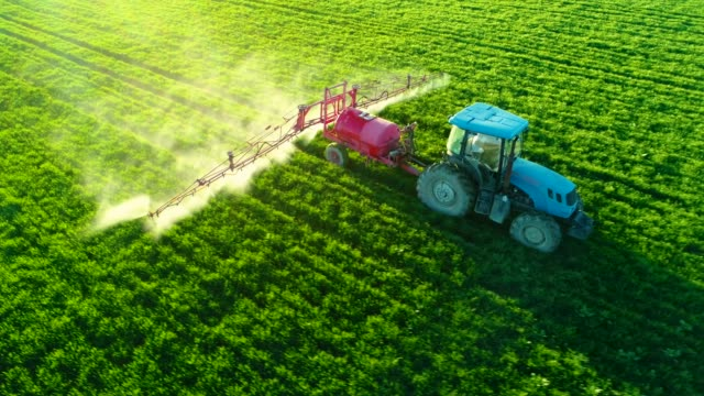 aerial view of farming tractor plowing and spraying on field - trattore video stock e b–roll