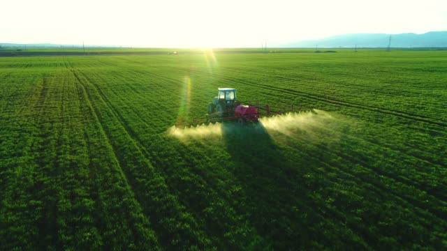 vídeos de stock e filmes b-roll de aerial view of farming tractor plowing and spraying on field - colheita