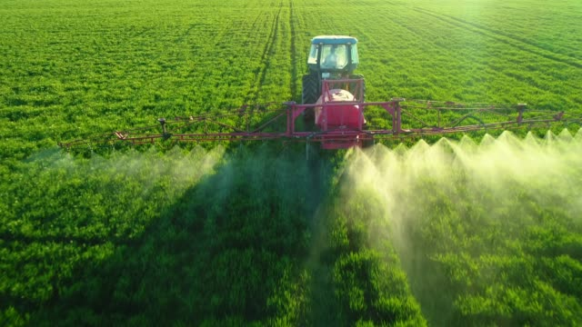vídeos de stock e filmes b-roll de aerial view of farming tractor plowing and spraying on green field - pulverizar
