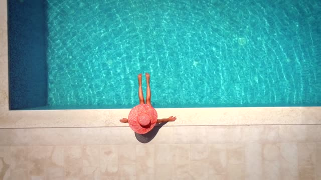 Aerial view of female with hat sitting by swimming pool. Aerial view of young girl in sunhat sitting by swimming pool. hotel stock videos & royalty-free footage