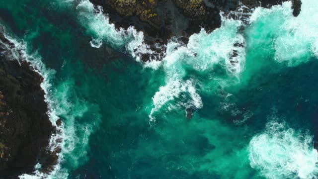 Video Aerial view of fierce waves splashing against rocks.