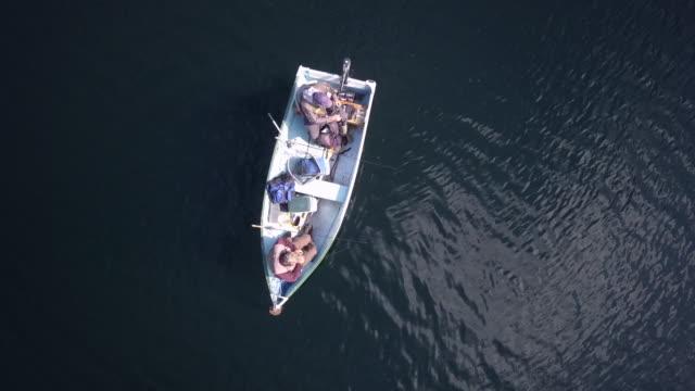 aerial view of fishermans fishing from a boat on lake - rybak filmów i materiałów b-roll