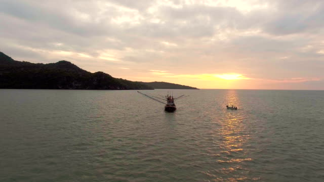 Aerial view of Fishing boat and mountain background with beautiful sunset video