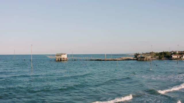 güneşli bir günde balıkçı kulübelerinin havadan görünümü - ravenna stok videoları ve detay görüntü çekimi