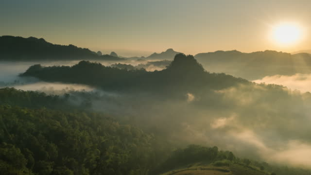 Aerial view of Fog rolls across flowing over rain forest mountain in the northern Thailand,Hyper lapse