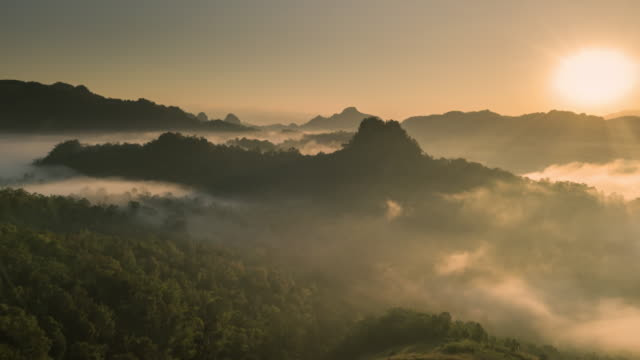 Aerial view of Fog rolls across flowing over rain forest mountain in the northern Thailand,Hyper lapse Aerial view of Fog rolls across flowing over rain forest mountain in the northern Thailand,Hyper lapse mountains in mist stock videos & royalty-free footage