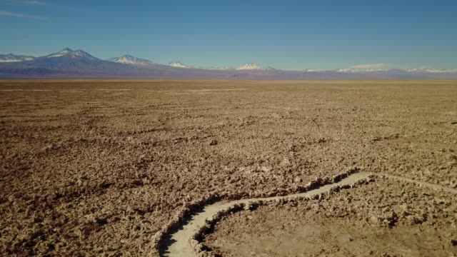 vídeos de stock e filmes b-roll de aerial view of footpath in the middle of salt flat in atacama desert with the background of blue clear sky and snowcapped mountain. - parque nacional do vale da morte