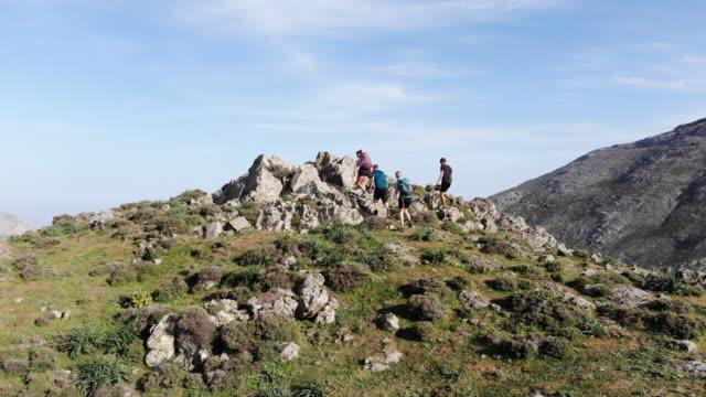 바다 전망 산 피크 마지막 피치를 등반 하는 4 명의 등산객의 항공 보기 - mountain top 스톡 비디오 및 b-롤 화면