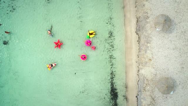 vídeos de stock, filmes e b-roll de vista aérea de amigos flutuando sobre colchões infláveis no mar transparente. - inflável