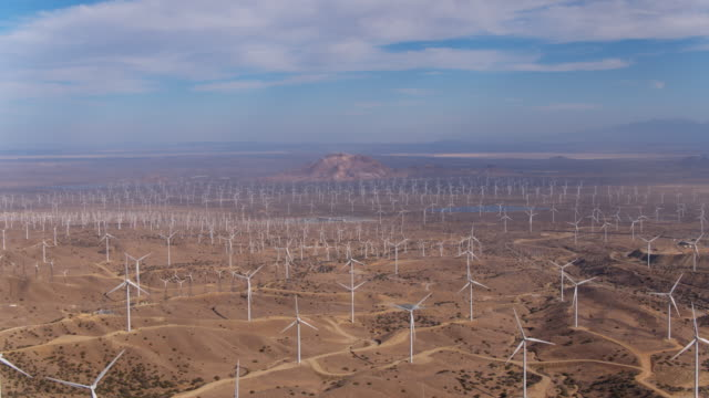 Aerial view of giant wind turbine field shot from above looking down creating clean renewable energy