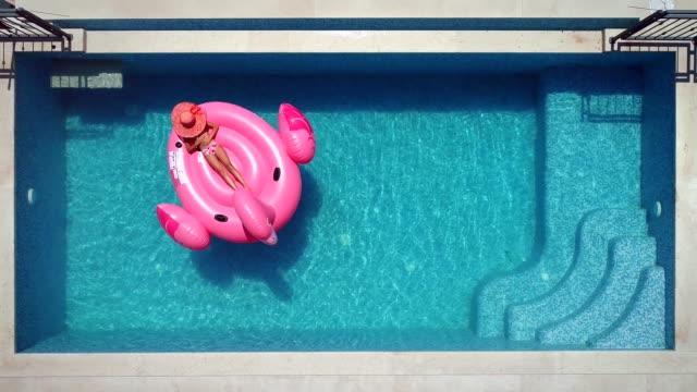 vídeos de stock, filmes e b-roll de vista aérea da menina deitada no flamingo inflável na piscina. - inflável