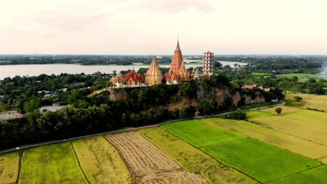 aerial view of golden pagoda on hill with rice paddy plantation at kanchanaburi, thailand - mountain top filmów i materiałów b-roll