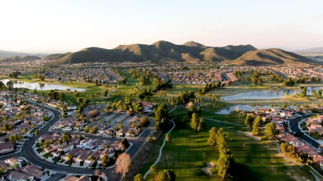 gün batımı nda şehir evleri ve lüks villalarla çevrili golf sahasının havadan görünümü, temecula - mountain top stok videoları ve detay görüntü çekimi