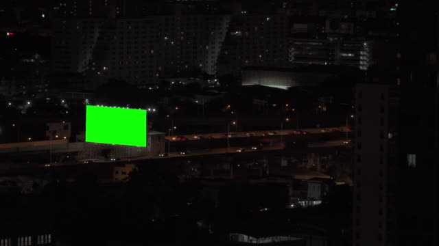 4K Aerial view of green screen or chroma key advertising display monitor billboard over city street with busy traffic driving cars on the road and highway illuminated night lights at downtown district.