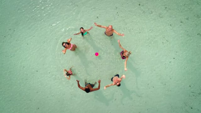 aerial view of group of friends in swimwear playing volleyball in sea near beach. - cerchio video stock e b–roll