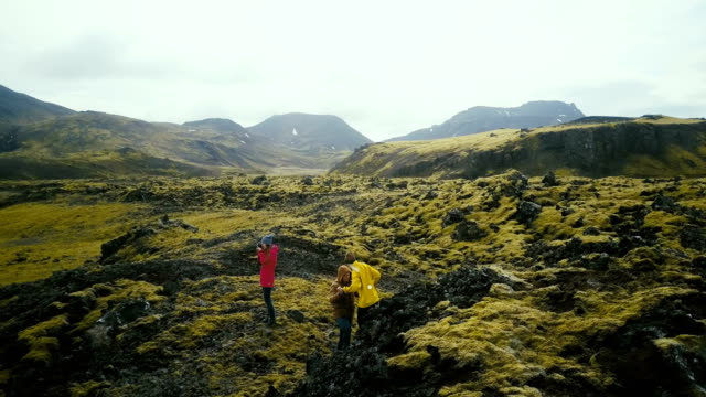Aerial view of group of tourists hiking on lava fields in Iceland. Woman photographer holding camera, waiting friends video