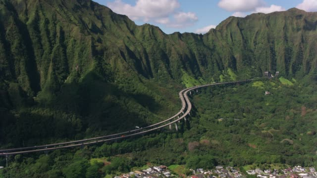Aerial view of H3 highway winding through mountains. Oahu, Hawaii circa-2018.  Aerial view of H3 highway winding through mountains.  Shot with Cineflex and RED Epic-W Helium. hawaii islands stock videos & royalty-free footage