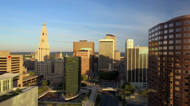 Aerial view of Hartford, CT skyline Aerial video, reversing from Hartford, CT skyline during spring morning sunrise , Connecticut Science Center, Phoenix Building, Mortensen Riverfront Plaza and Gold Building included. connecticut stock videos & royalty-free footage