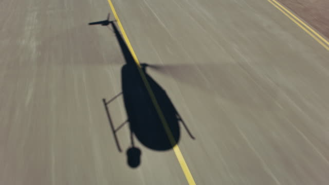 Aerial view of helicopter shadow on runway