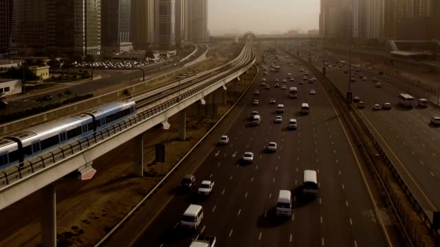 Aerial view of high-speed trains blue, which travels through the overpass along the highway with cars surrounded by skyscrapers. Dubai, UAE video