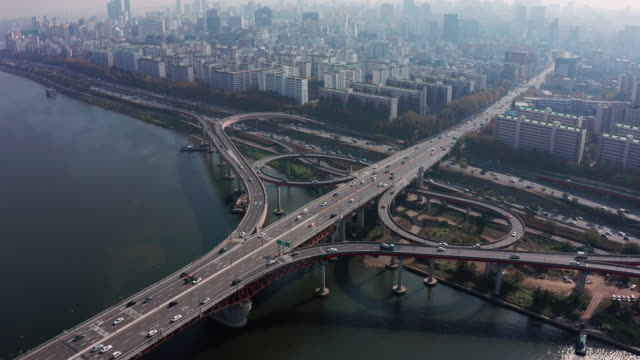 Aerial view of Highway road junctions. The Intersecting freeway road overpass of Seoul downtown city skyline with vehicle on expressway and bridge cross over Han river in Seoul city, South Korea. Aerial view of Highway road junctions. The Intersecting freeway road overpass of Seoul downtown city skyline with vehicle on expressway and bridge cross over Han river in Seoul city, South Korea. namsan seoul stock videos & royalty-free footage