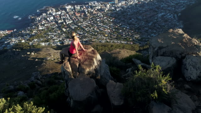 Aerial view of hiker female on top of mountain Aerial view of a young woman on the top of Lion's head mountain in Cape Town, South Africa. cape peninsula stock videos & royalty-free footage