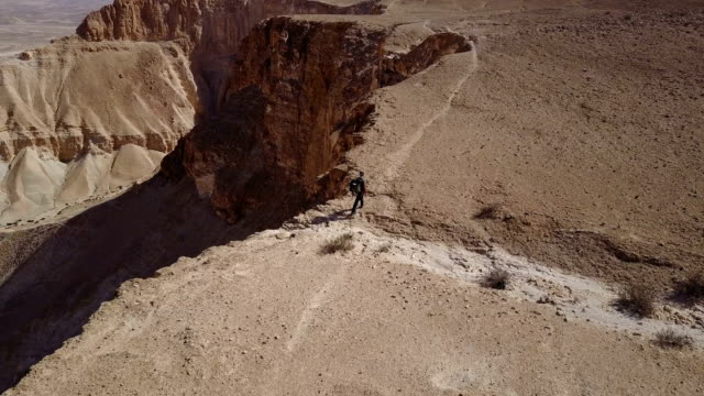 aerial view of hiker hiking on mountains in desert - засушливый климат стоковые видео и кадры b-roll