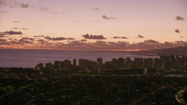 Aerial view of Honolulu and Waikiki at dusk. Honolulu, Oahu, Hawaii circa-2018.  Aerial view of Honolulu and Waikiki at dusk.  Shot with Cineflex and RED Epic-W Helium. waikiki stock videos & royalty-free footage