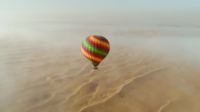 Aerial view of hot-air-balloon flying in the clouds on desert in Dubai, U.A.E. Aerial view of hot-air-balloon flying in the clouds of the Murqquab desert in Dubai, U.A.E. hot air balloon stock videos & royalty-free footage