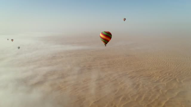 aerial view of hot-air-balloon flying in the clouds on desert in dubai, u.a.e. - dubai video stock e b–roll
