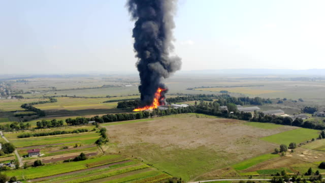 Aerial view of Huge fire view from quadcopter. Black smoke rises high into the sky. Fire on the outskirts of the city