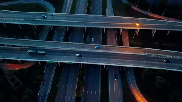 Aerial view of illuminated road interchange or highway intersection at sunset twilight - vídeo