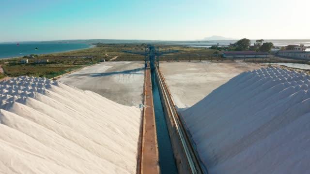 aerial view of industrial extraction of salt in the desert, pile of salt - соль минерал стоковые видео и кадры b-roll