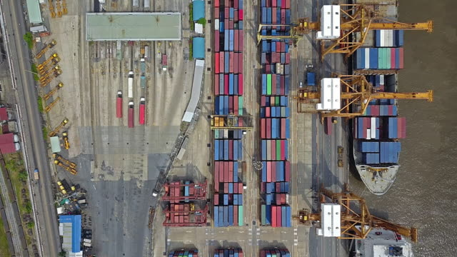 veduta aerea del porto industriale con nave container - costa caratteristica costiera video stock e b–roll