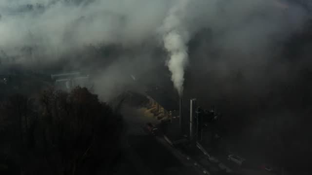 flygfoto av industriella smog kommer ut från en fabrik skorsten i ett landskap som täcks av dimma banker. - kol bildbanksvideor och videomaterial från bakom kulisserna