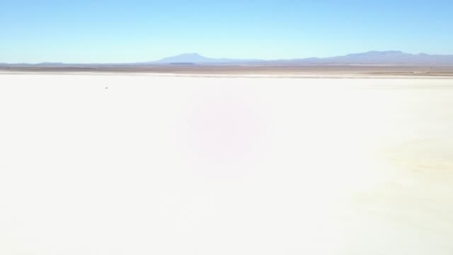 Aerial view of infinity white land of salt flat with the background of mountain range and clear blue sky. The footage was taken in Salar de Uyuni, Bolivia salt flat stock videos & royalty-free footage