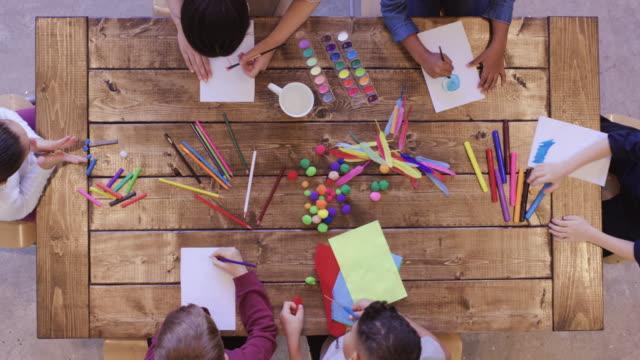 vidéos et rushes de vue aérienne des enfants faisant des arts et de l'artisanat - fournitures scolaires
