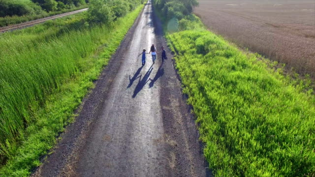 Aerial View of Kids Running Down Dirt Road video