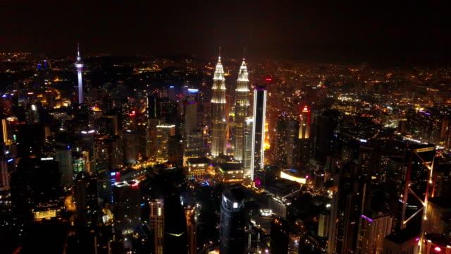 flyg foto över kuala lumpur downtown, malaysia. finans distrikt och affärs centra i smart urban stad i asien. sky skrapa och höghus på natten. - petronas twin towers bildbanksvideor och videomaterial från bakom kulisserna